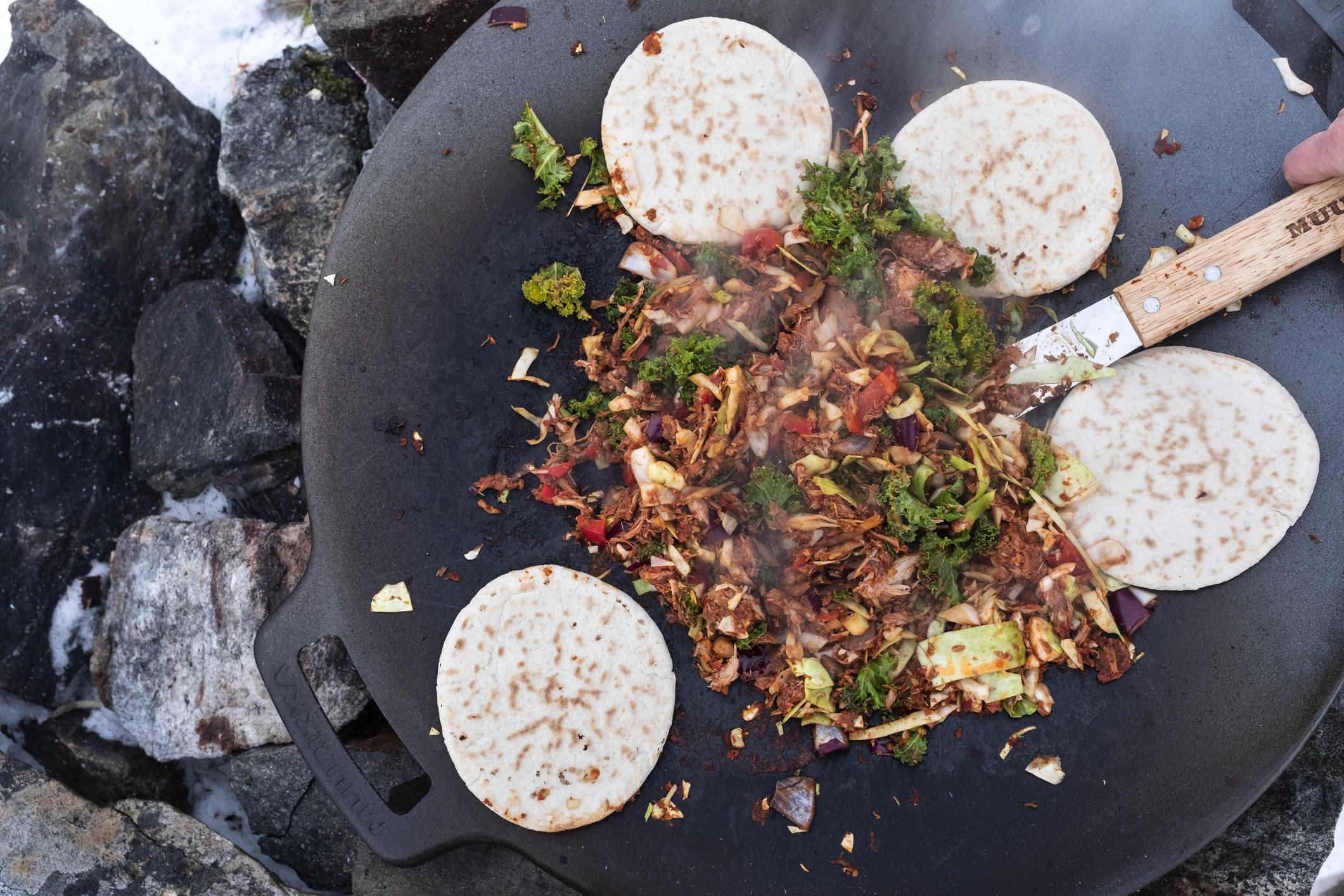Cooking tortillas and stir fry on a grill.