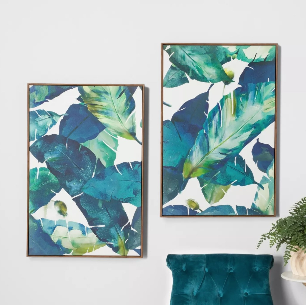 the two framed palm leaf prints hung on a wall