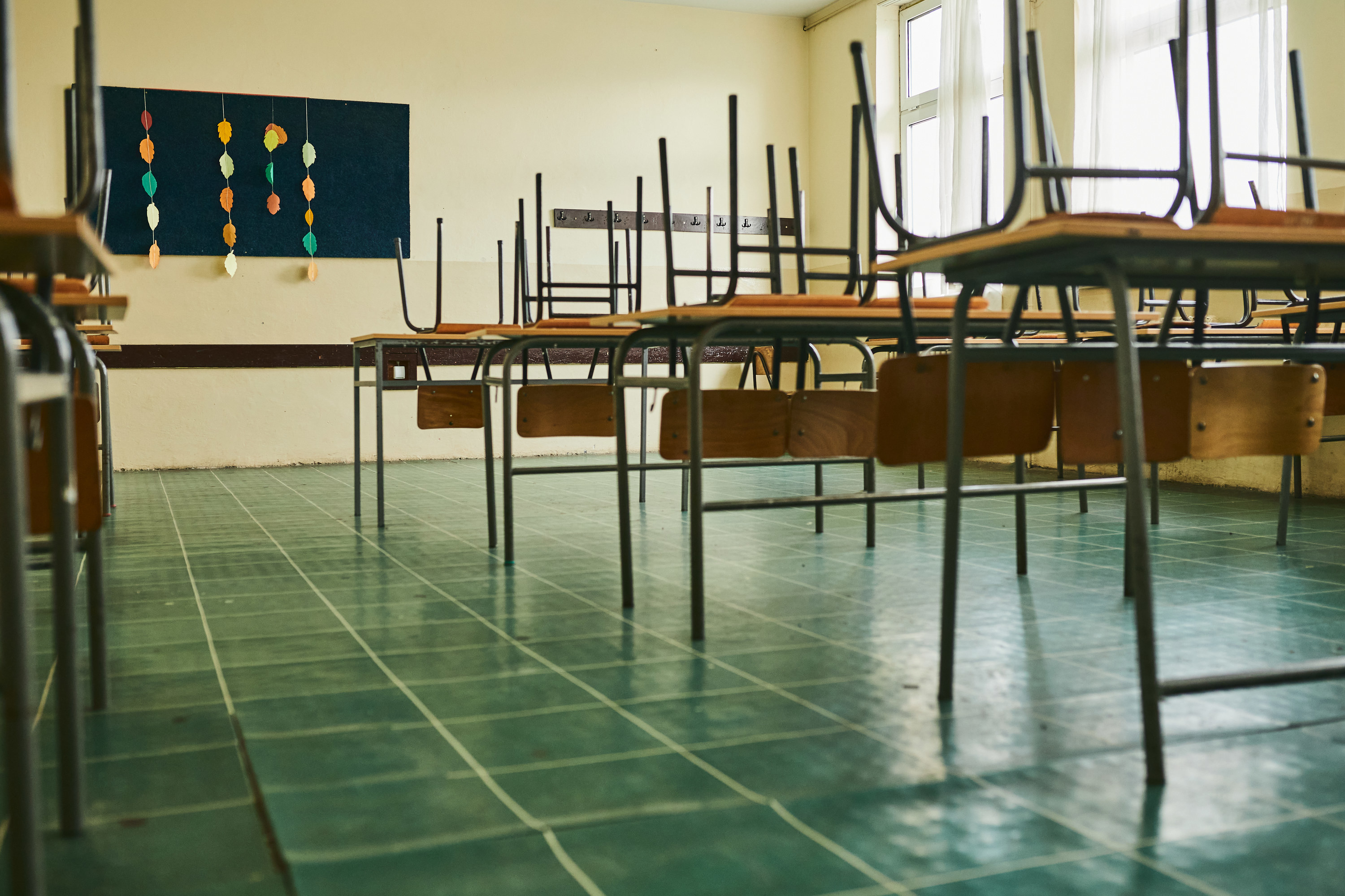 A classroom with the chairs up on the desks