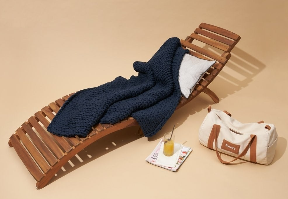 a navy blue knit weighted blanket on a lounge chair