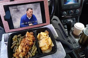 A reviewer photo of an iPad and food on a tray attached to the steering wheel of a car
