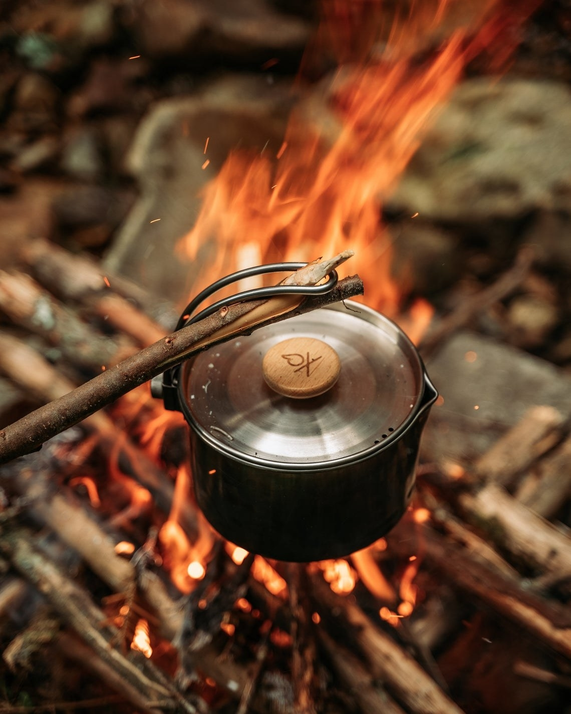 the pot held over a fire with a stick