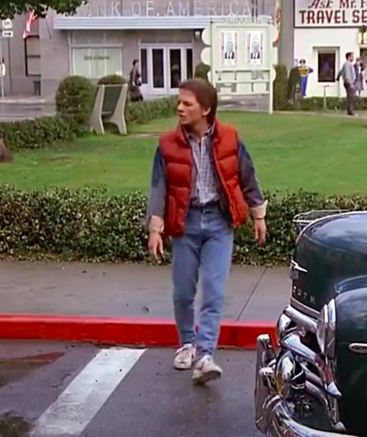 Marty McFly wearing sneakers, jeans, a-t shirt, a button-up, a jean jacket, and a vest