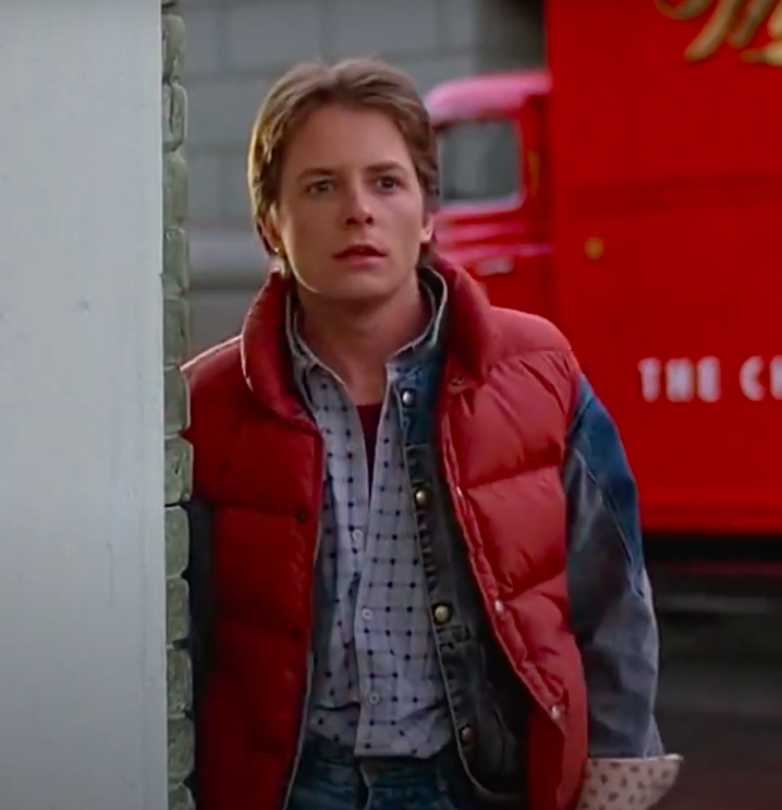 Marty McFly wearing sneakers, jeans, a button-up, a jean jacket, and a vest