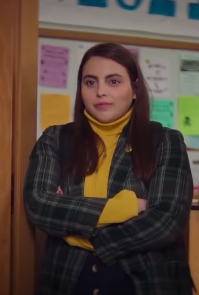 Amy wearing tights, a mini skirt, a turtleneck, and a blazer