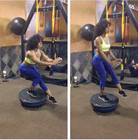 Woman balancing on ball while doing pistol squat
