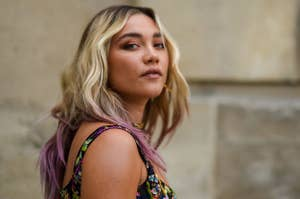 Florence Pugh looks over her shoulder at the camera as she wears a floral tank top dress