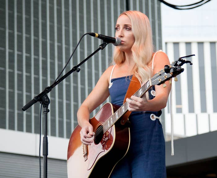 Ashley looks into the distance whileplaying an acoustic guitar onstage