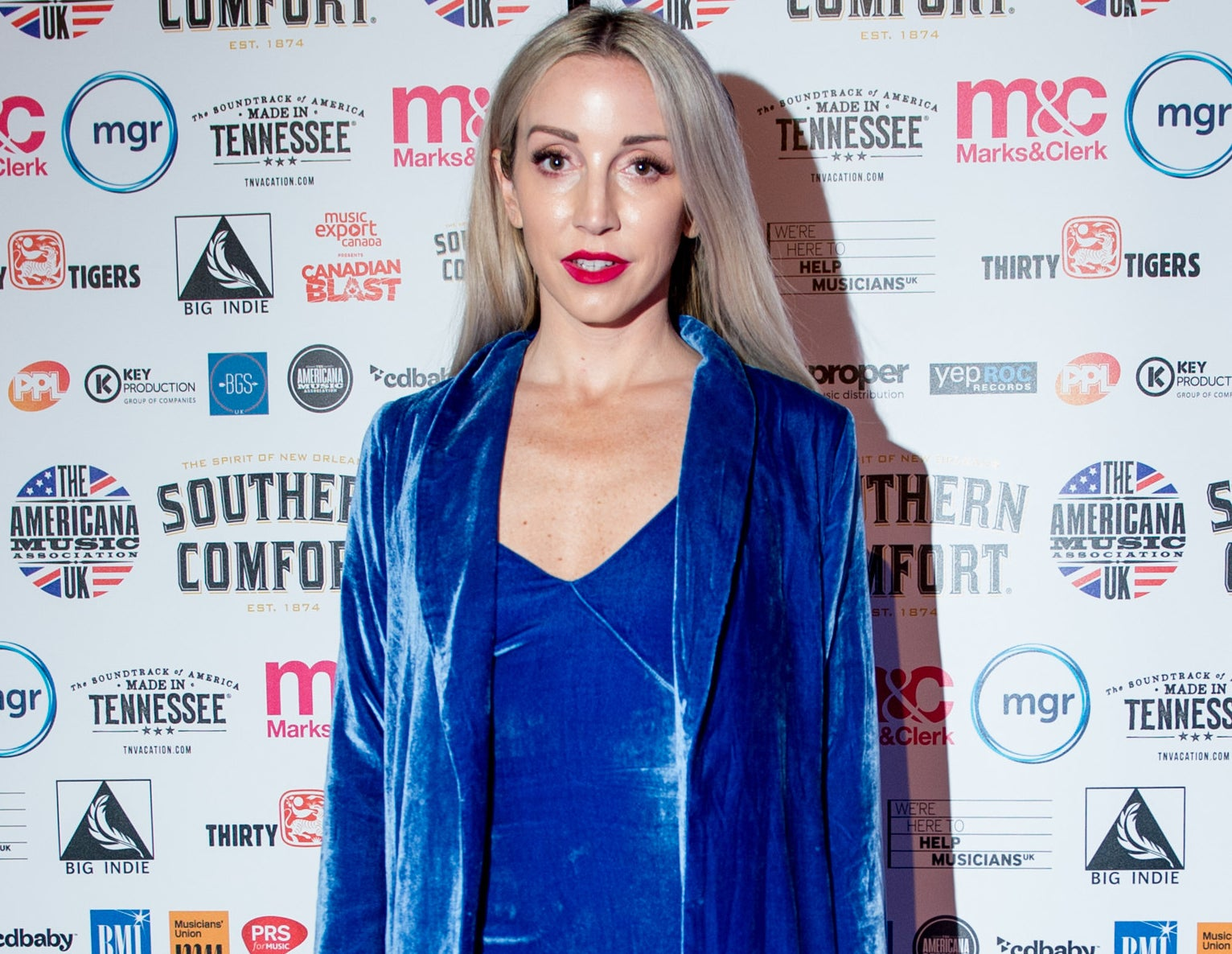 Ashley wears a blue velvet dress and blazer while on a red carpet