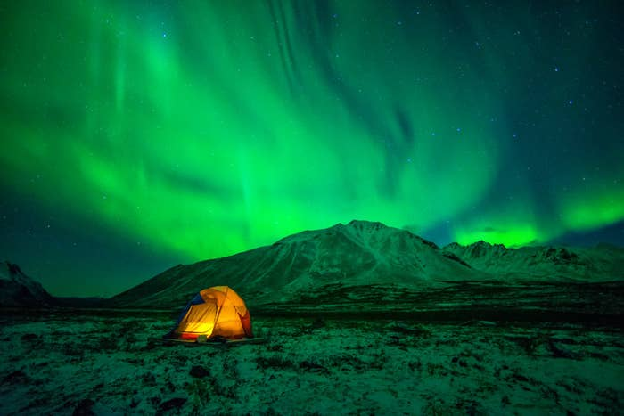 Tent camping under Northern Lights (Aurora Borealis) at Tombstone Territorial Park in Yukon.