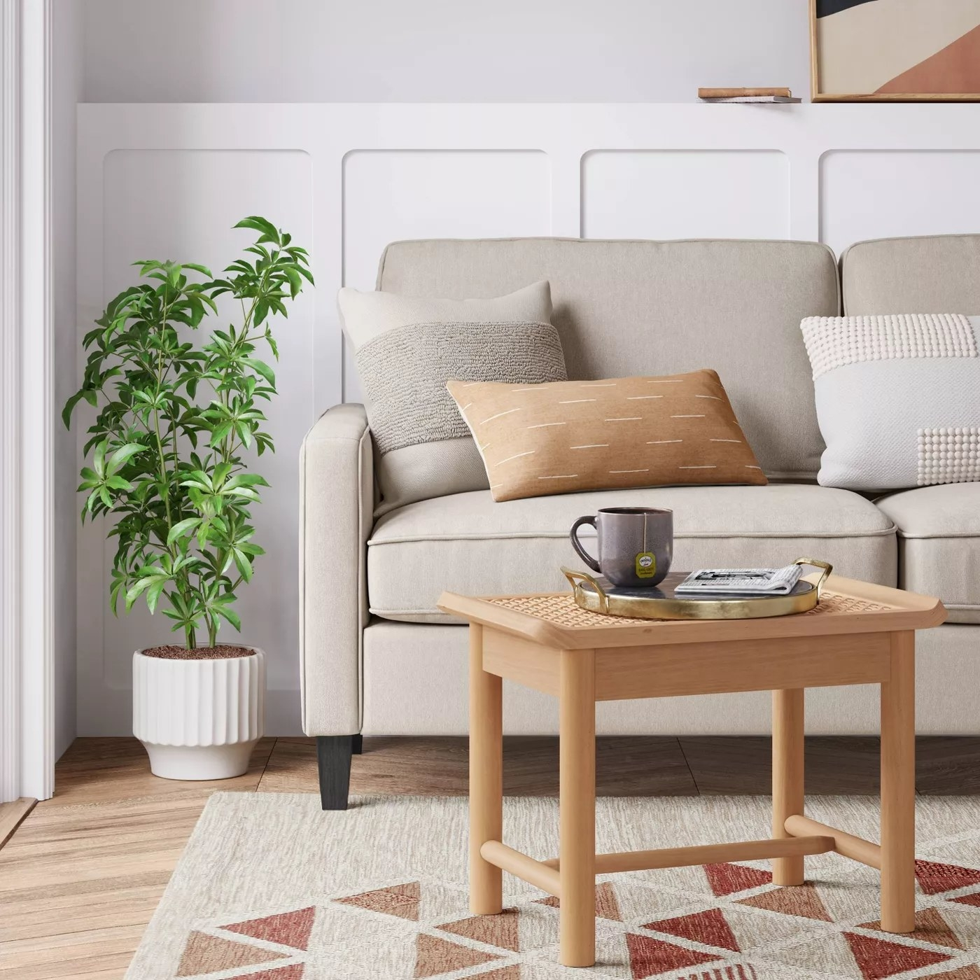 The light wood cane ottoman being used as a table in a living room