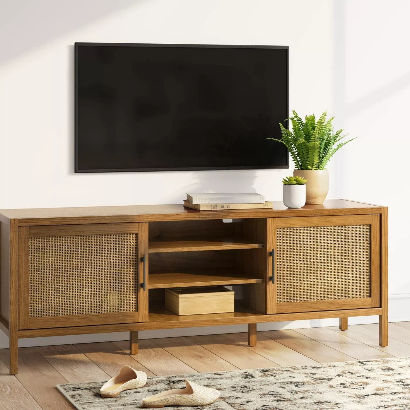 The TV stand with three open shelves in the center and two doors with more storage on either side