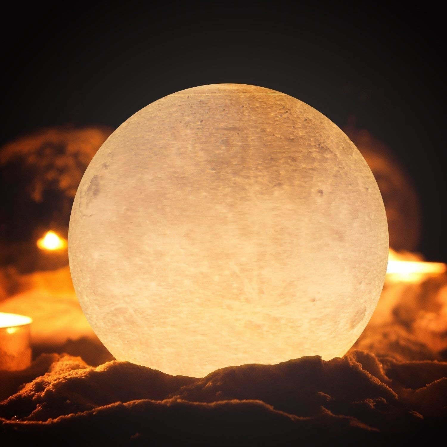 A moon shaped lamp with some sand and some candles