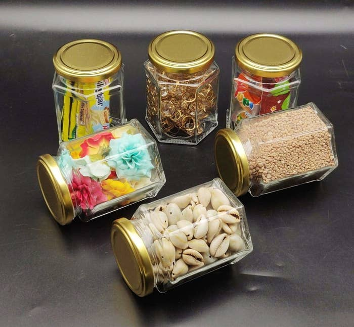 Different food items in hexagonal jars with golden rimmed lids