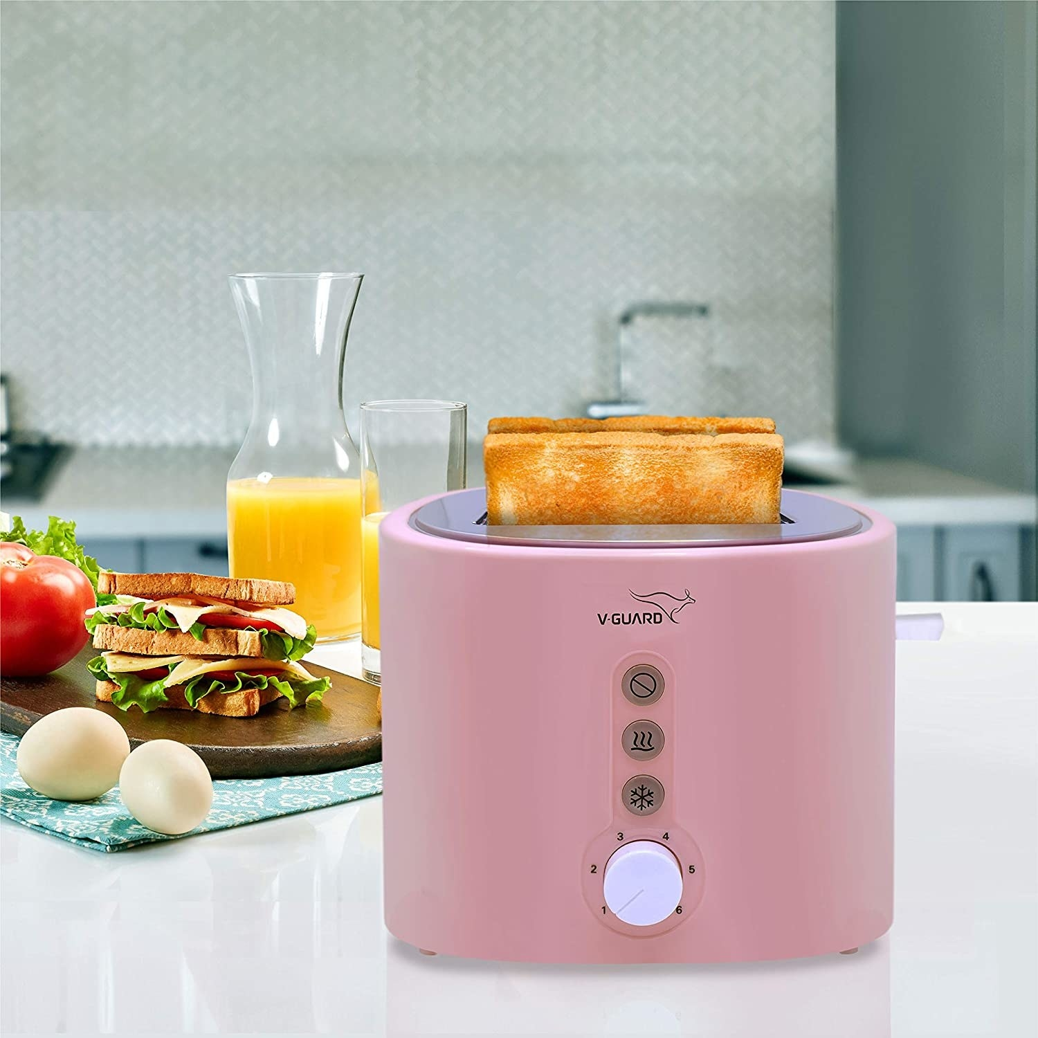 A pink pop-up toaster on a counter next to a sandwich with eggs