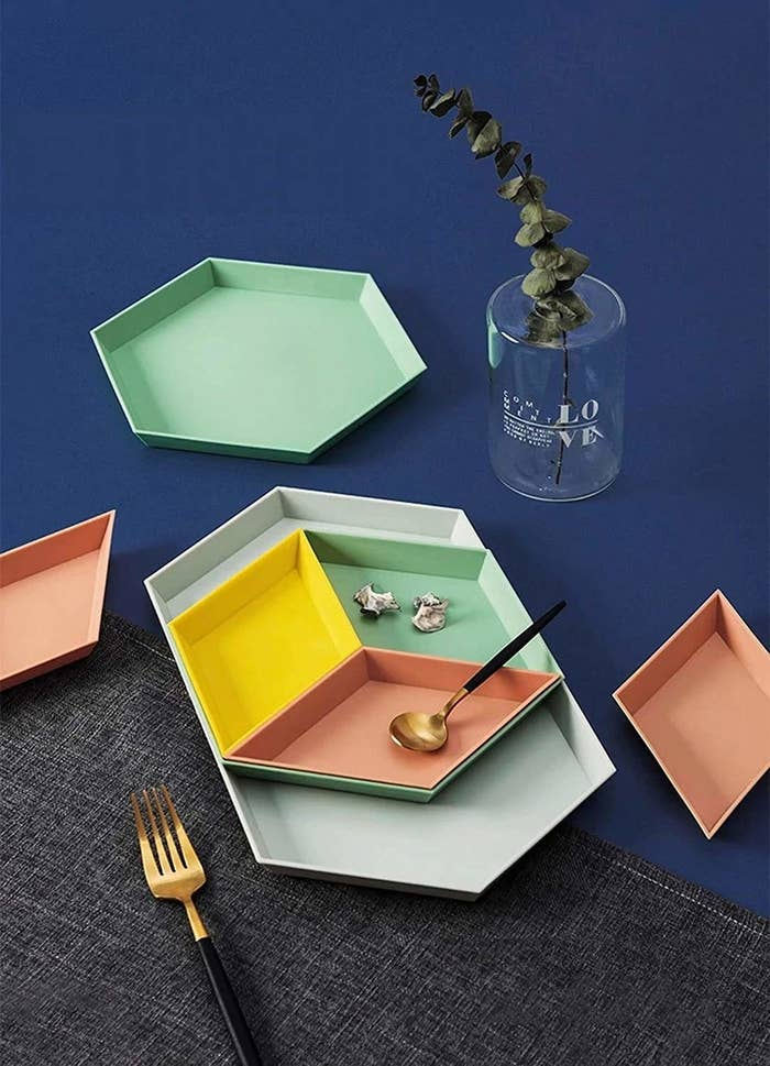 Pastel hexagonal organisers with a golden fork and a golden spoon near them