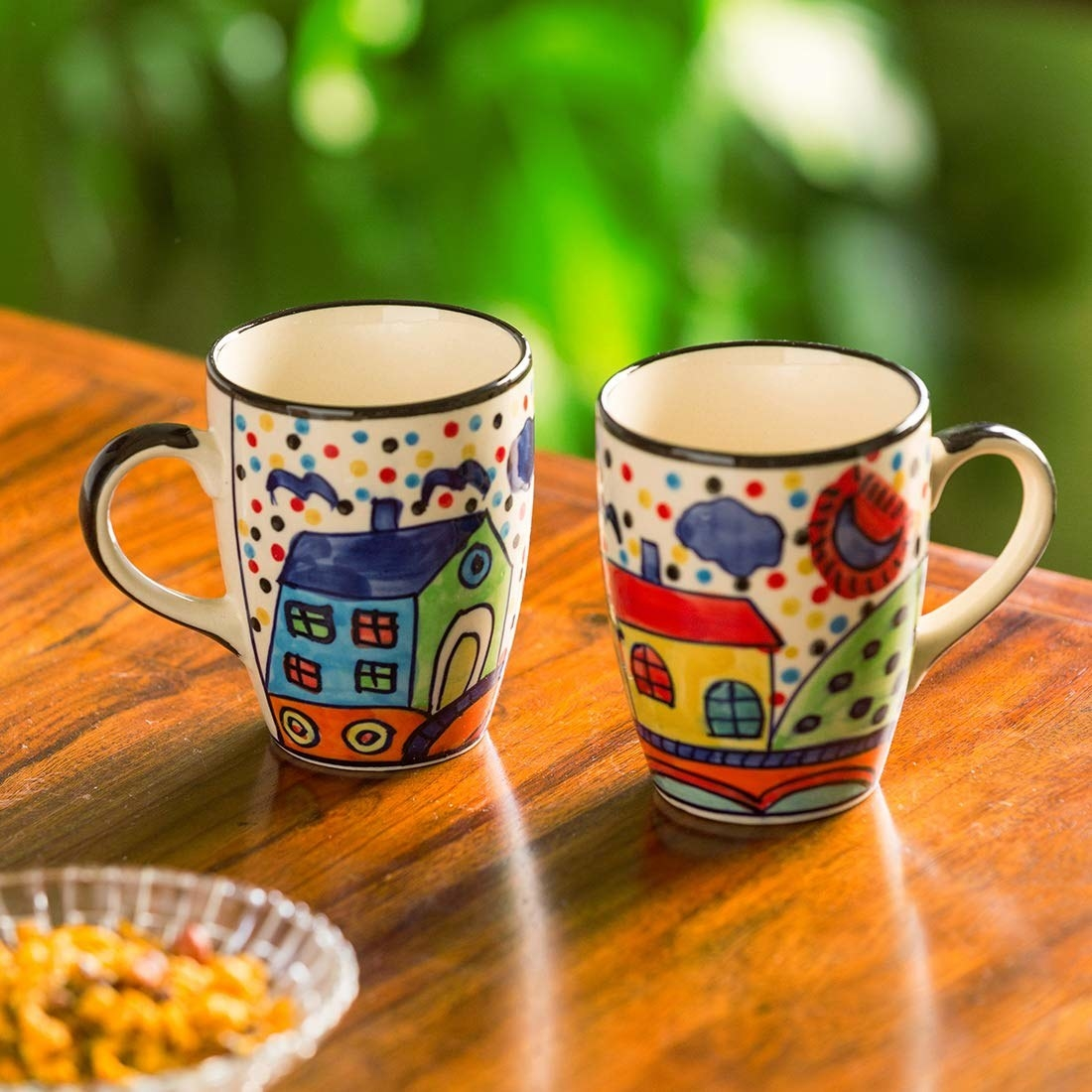 Two mugs with little houses hand-painted on them