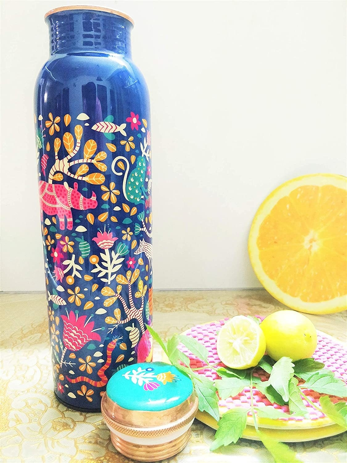 A blue copper water bottle with floral patterns