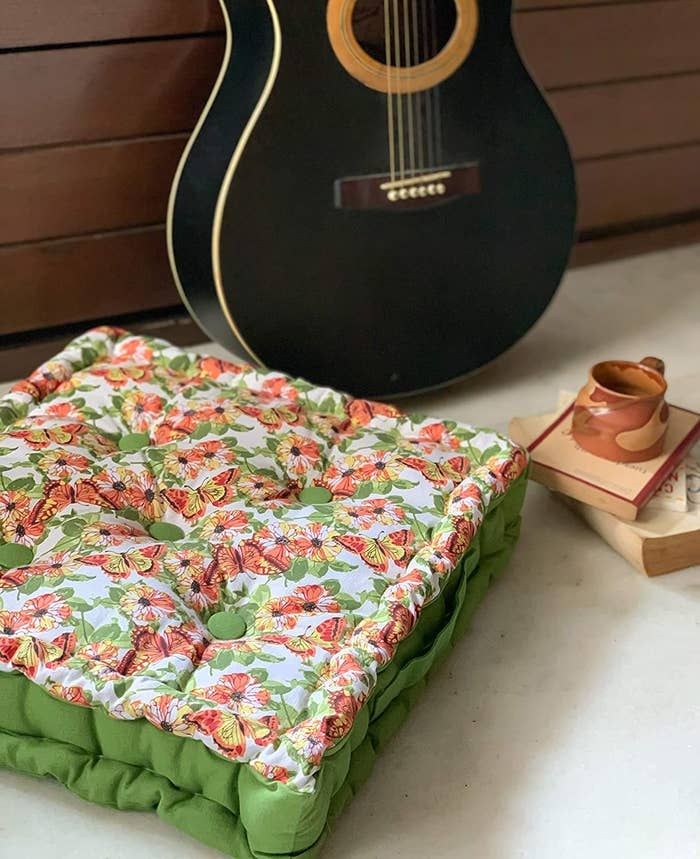 A green floor pillow with a butterfly pattern on it