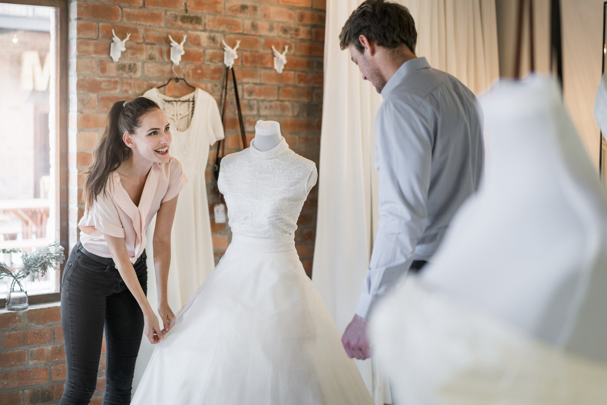 Woman and man admiring a wedding gown on a headless mannequin