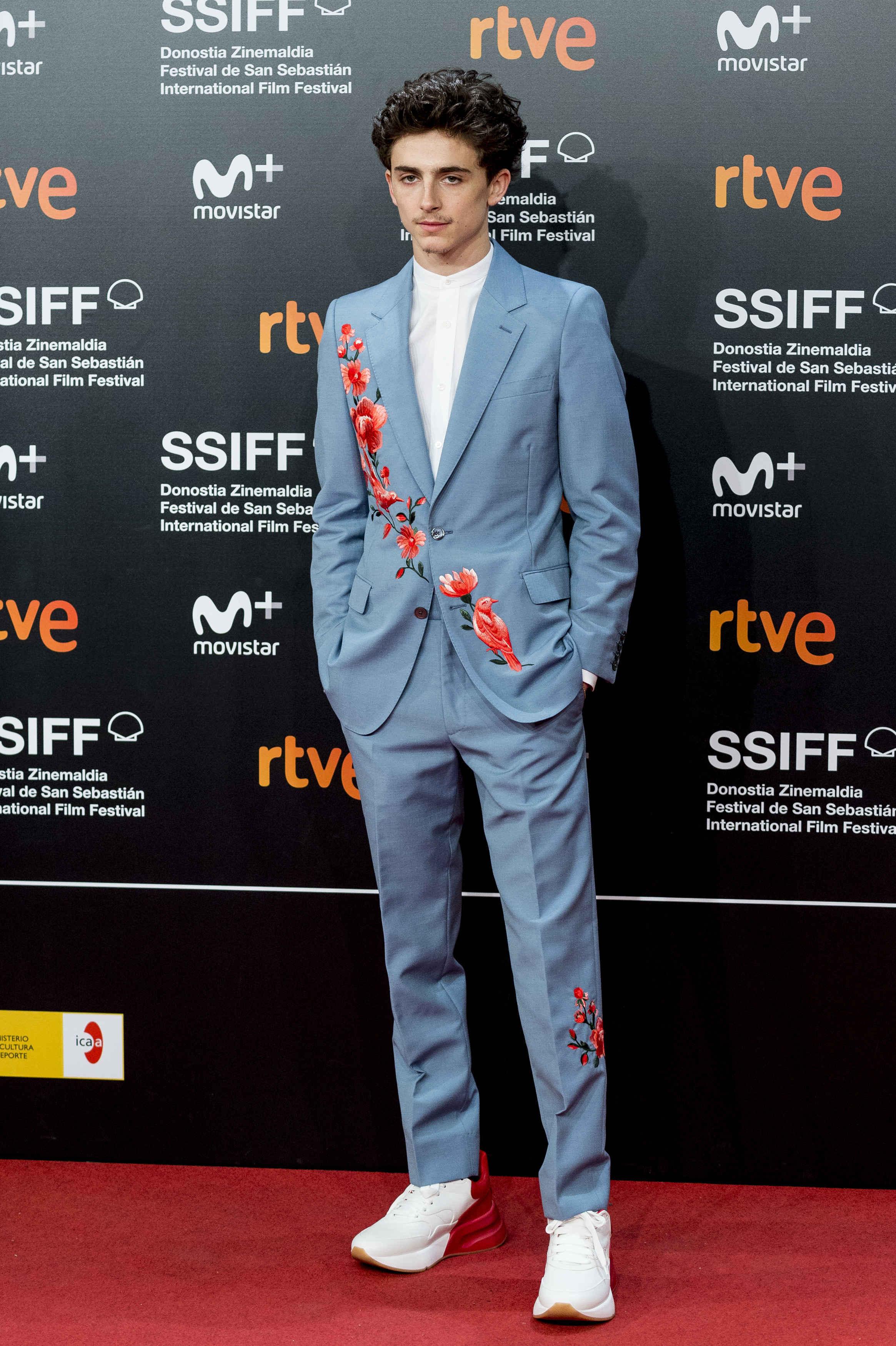 Timothée wears a light blue suit with embroidered red flowers across the chest