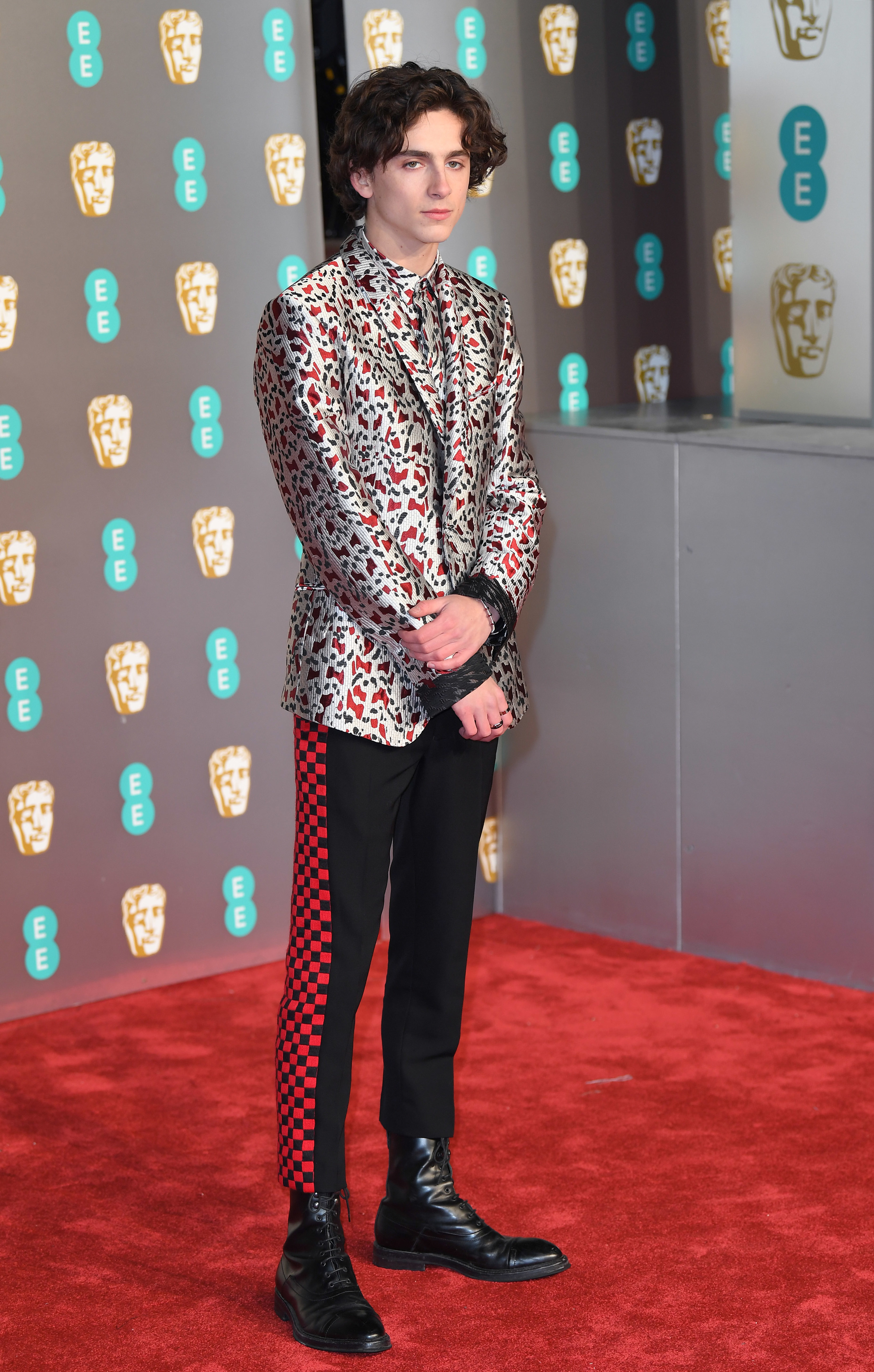 Timothée wears a grey and red patterned suit and black pants with red checkered detailing on the side