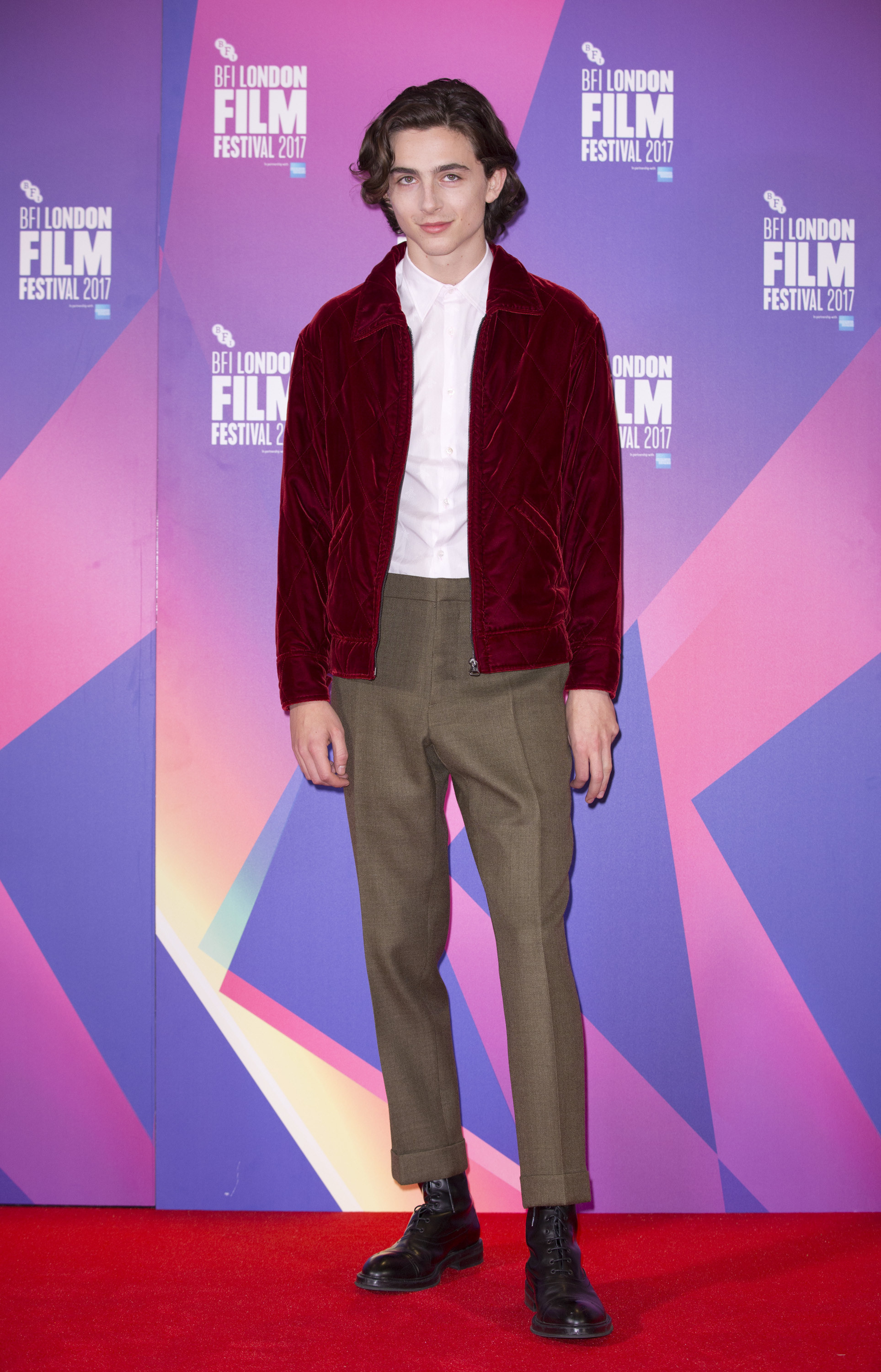 Timothée wears a maroon bomber jacket, white button down, and brown tailored pants