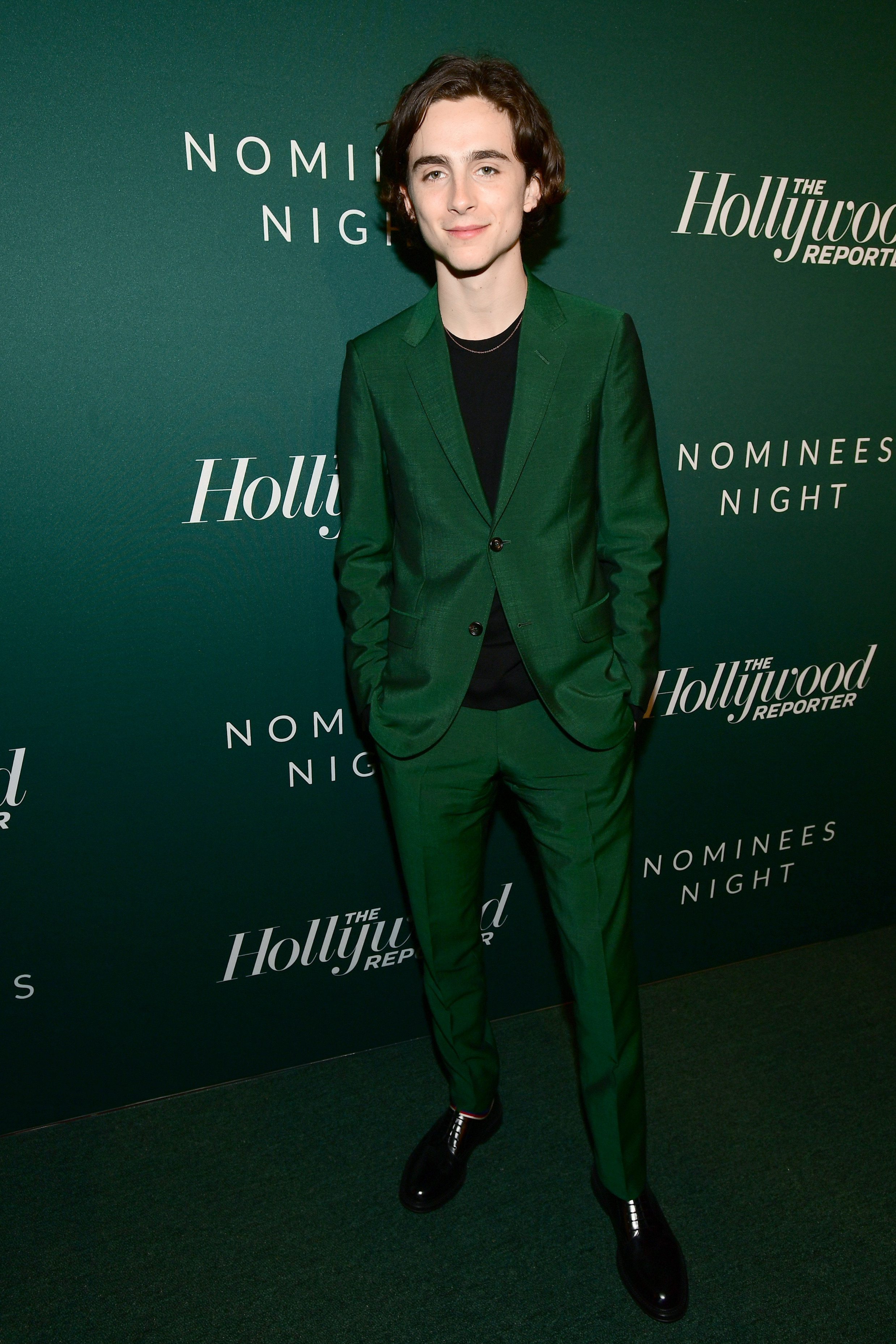 Timothée wears a forest green suit in front of the same color backdrop and carpet