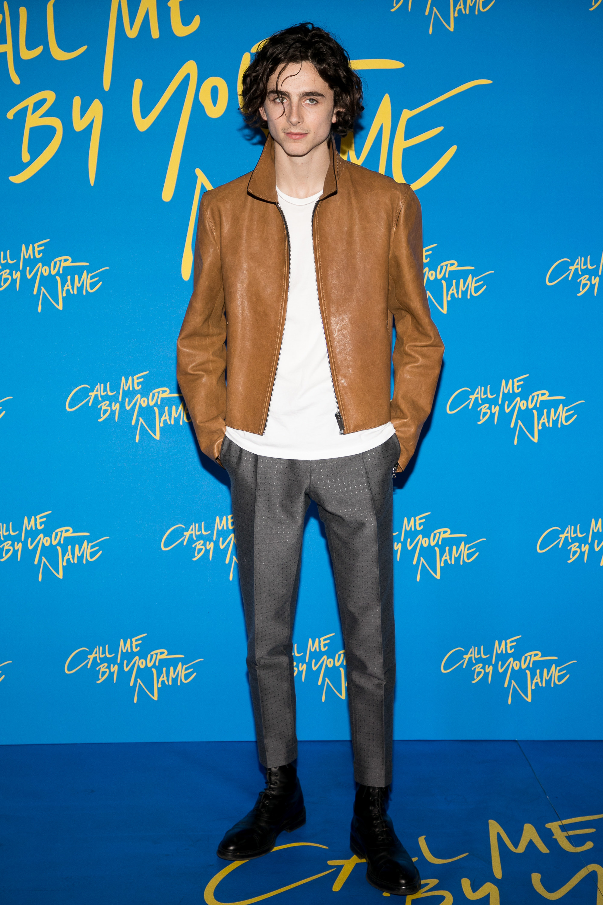 Timothée wears a brown leather jacket, a white tee, and grey suit pants