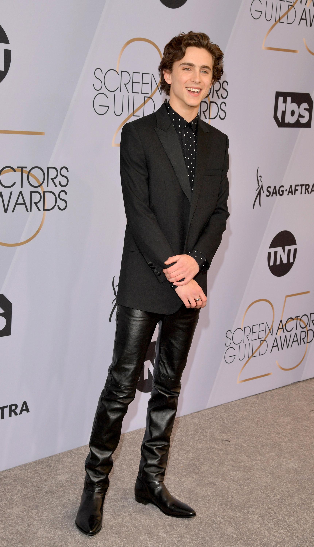 Timothée wears a black blazer with straight leg black leather pants