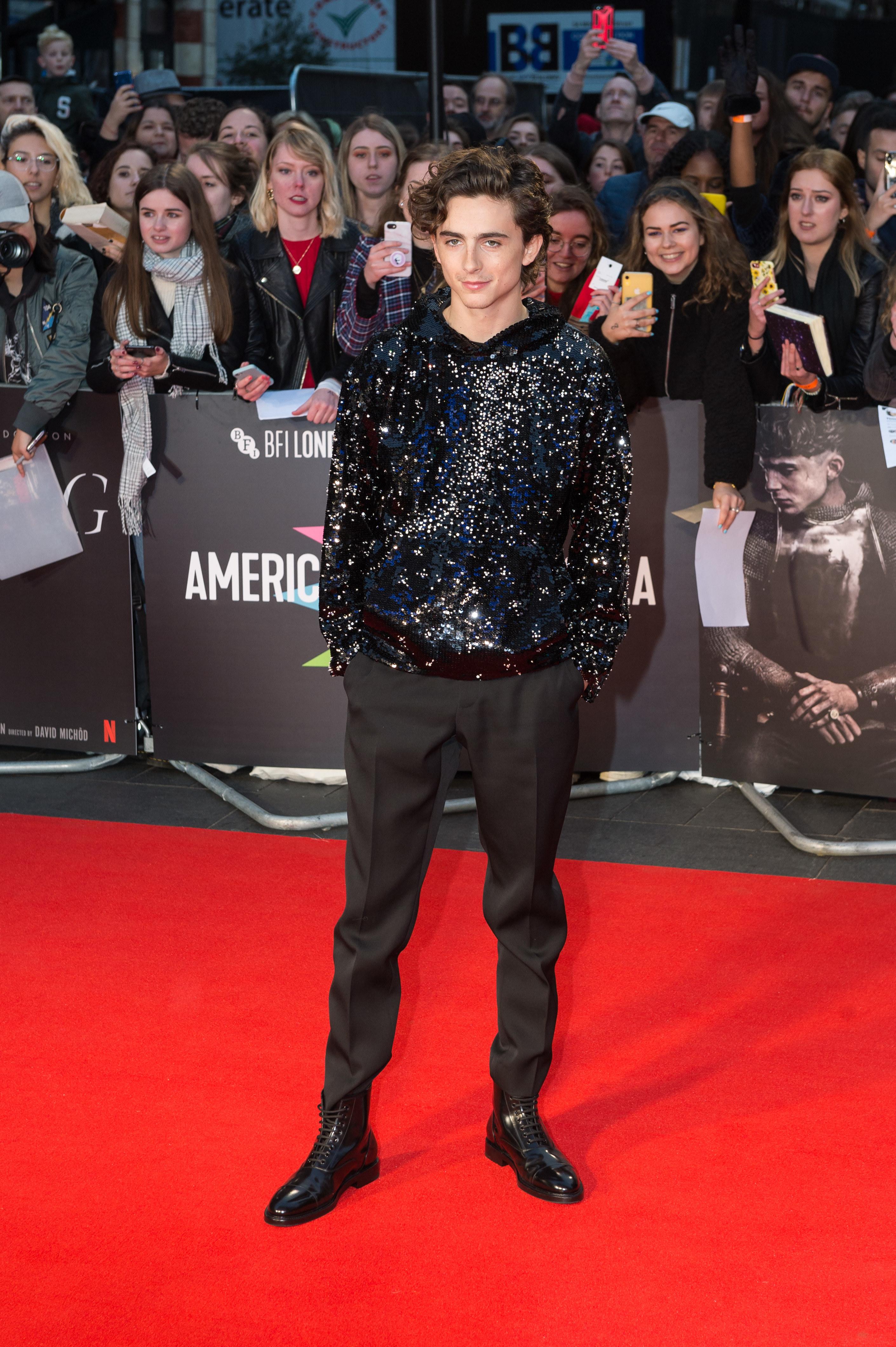 Timothée wears a shimmering black hoodie and black suit pants