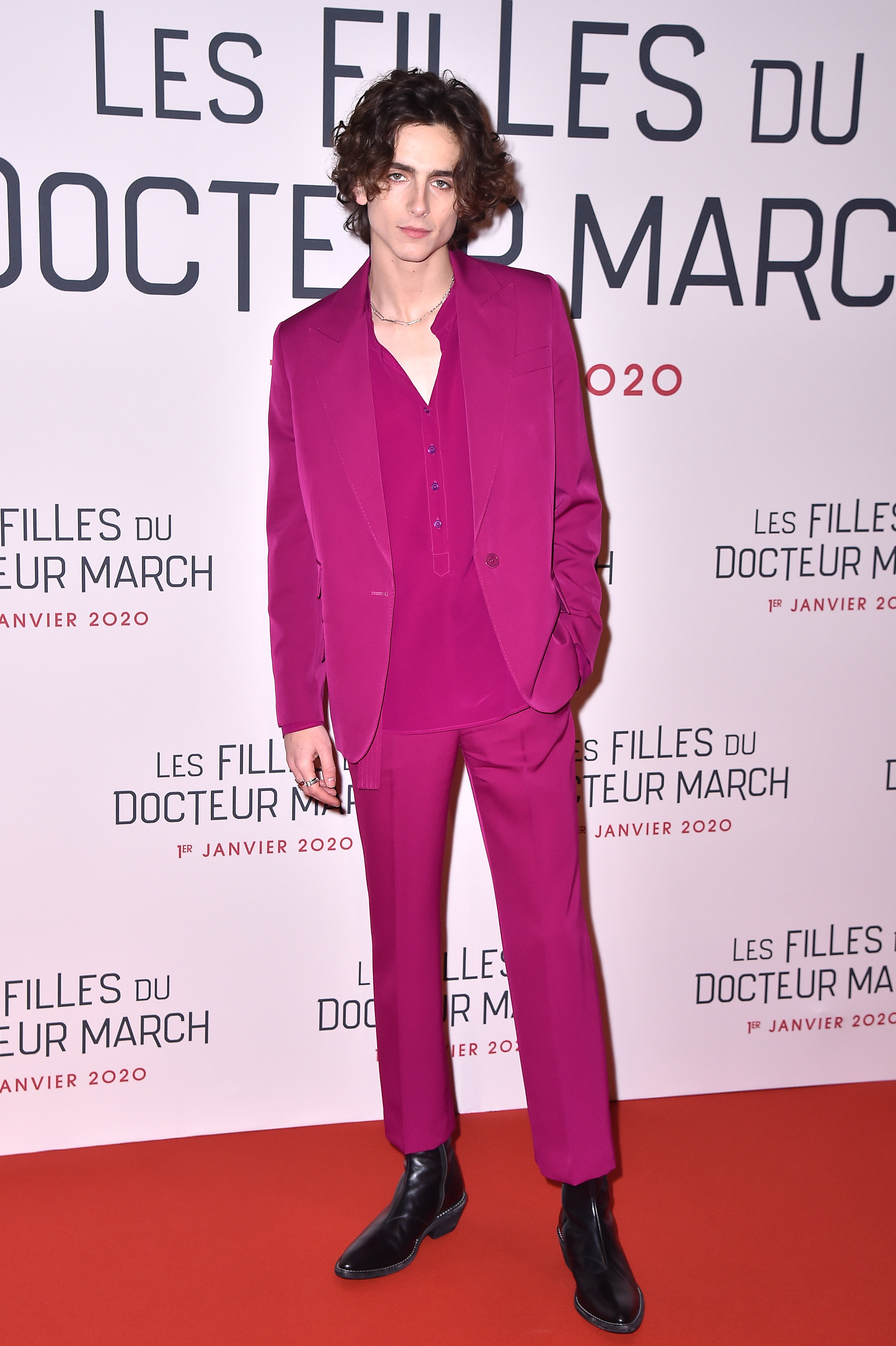 Timothée wears a fuchsia suit with a matching half button down top