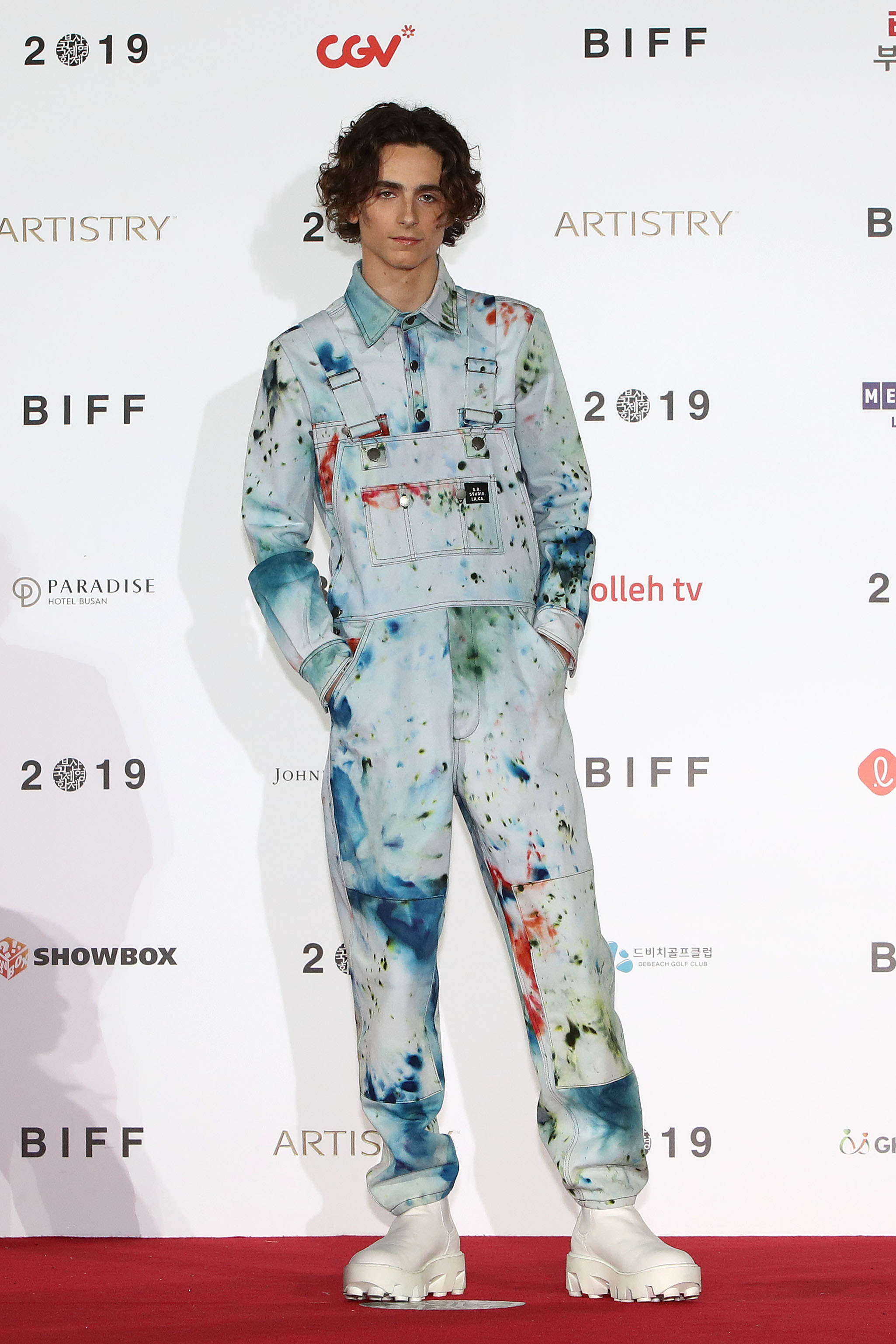 Timothée wears splatter-painted overalls with a matching long sleeve button down