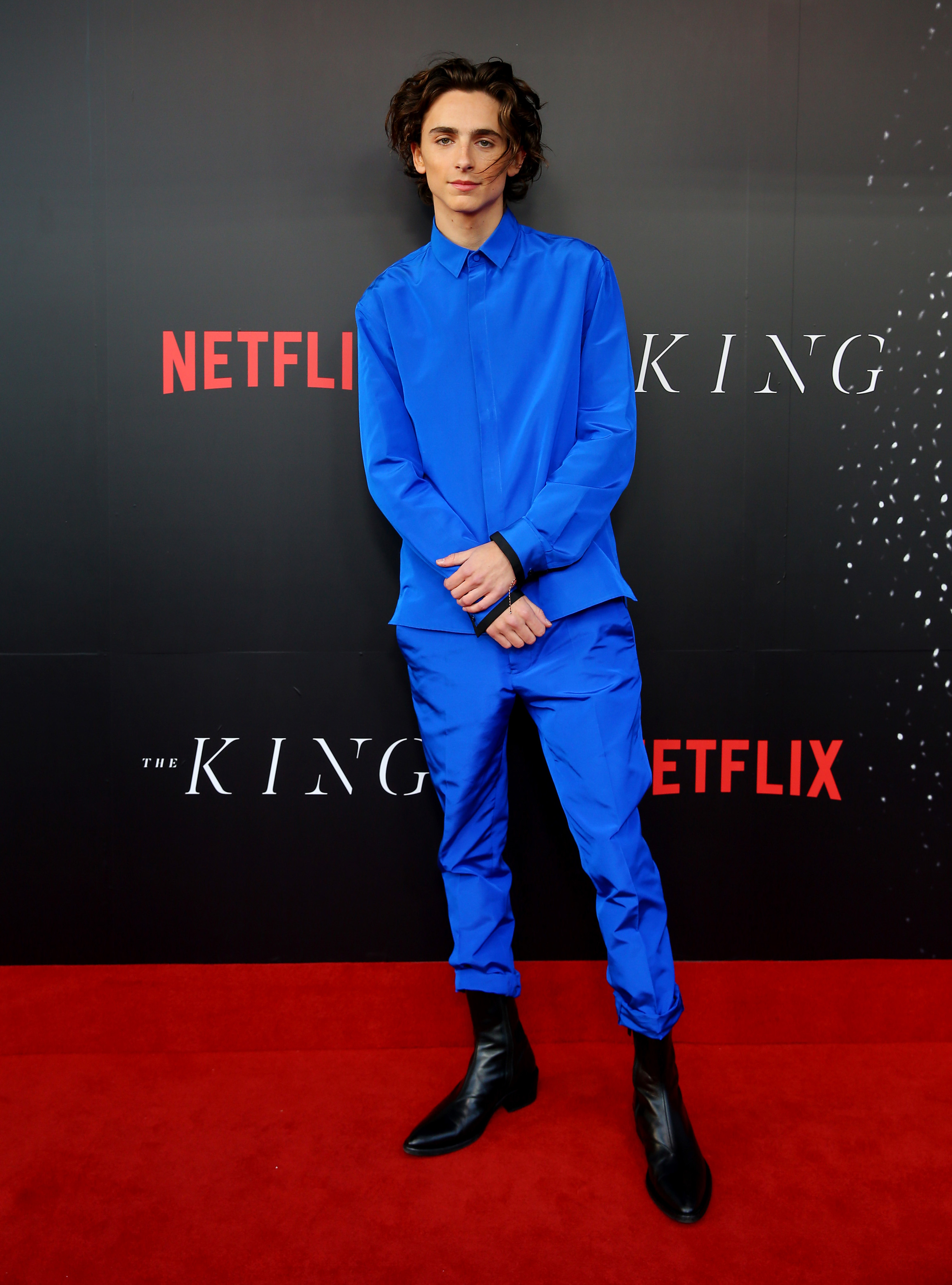Timothée wears a royal blue button down and matching pants with black boots