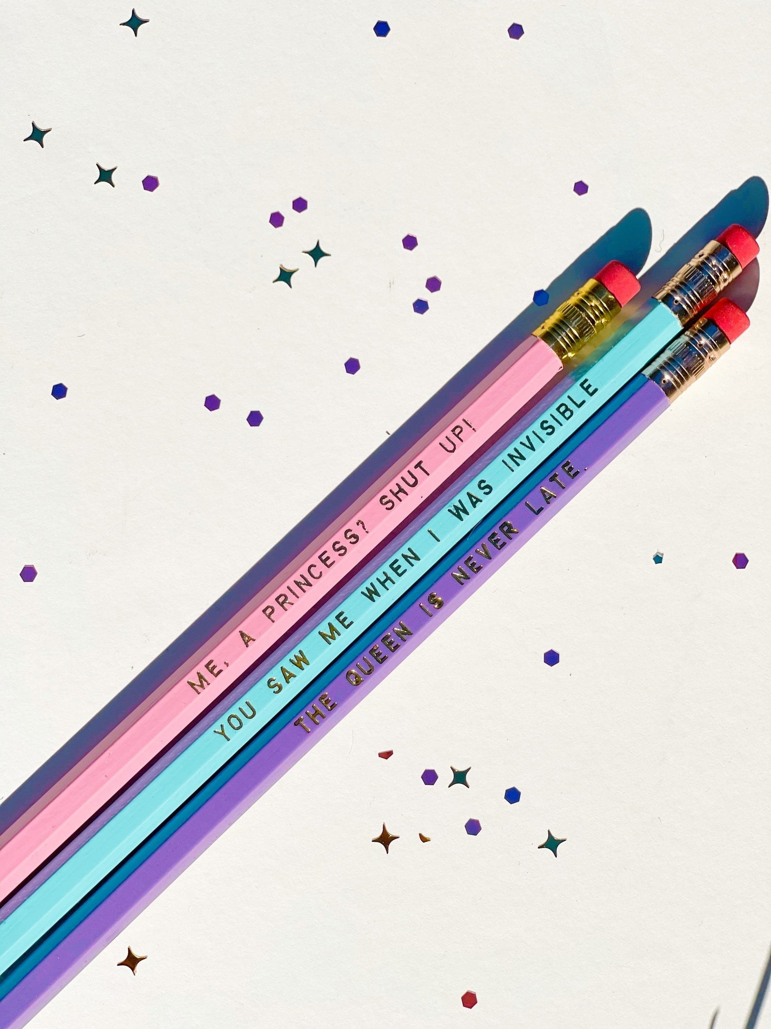 """a pink pencil that says """"me, a princess? shut up!"""" a blue pencil that says """"you saw me when I was invisible"""" and a purple pencil that says """"The queen is never late"""""""