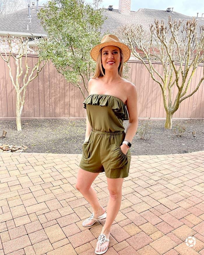 reviewer wearing green romper outside