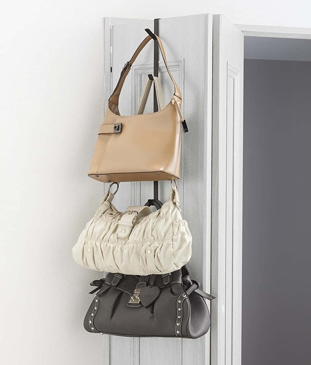 Three bags stacked on top of each other, hanging off of the over-door hanger