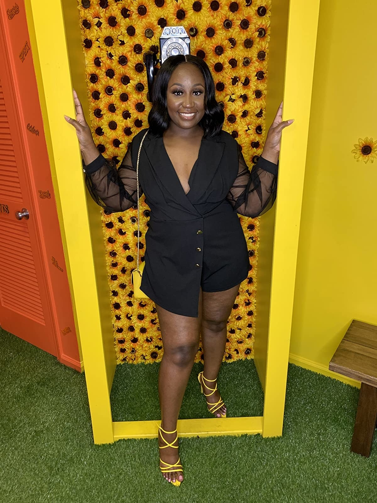a reviewer wearing the black notch collar romper in a size large