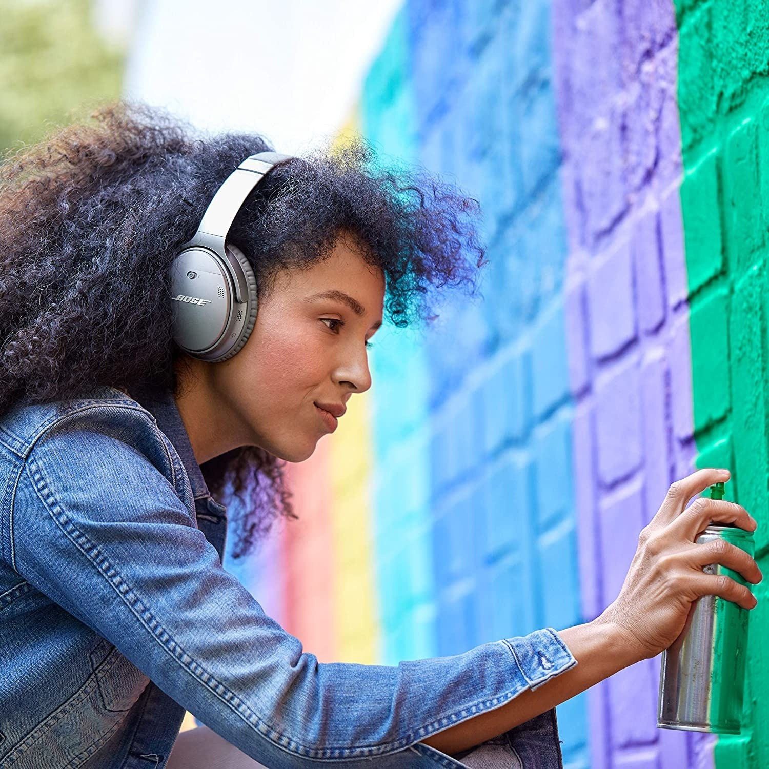 Artist spray painting a wall while wearing headphones