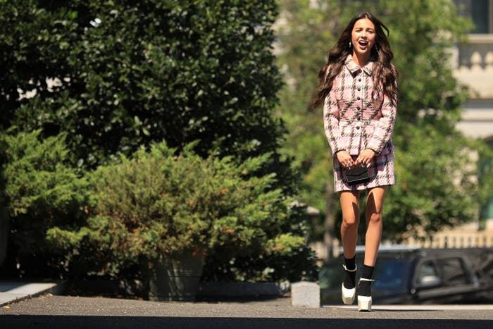Olivia Rodrigo wearing a plaid dress and jacket walks to the White House