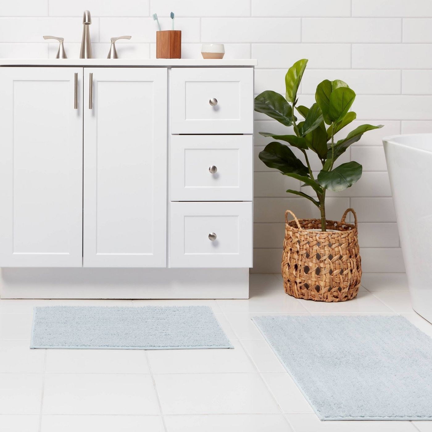two light blue bath mats staged in a bathroom