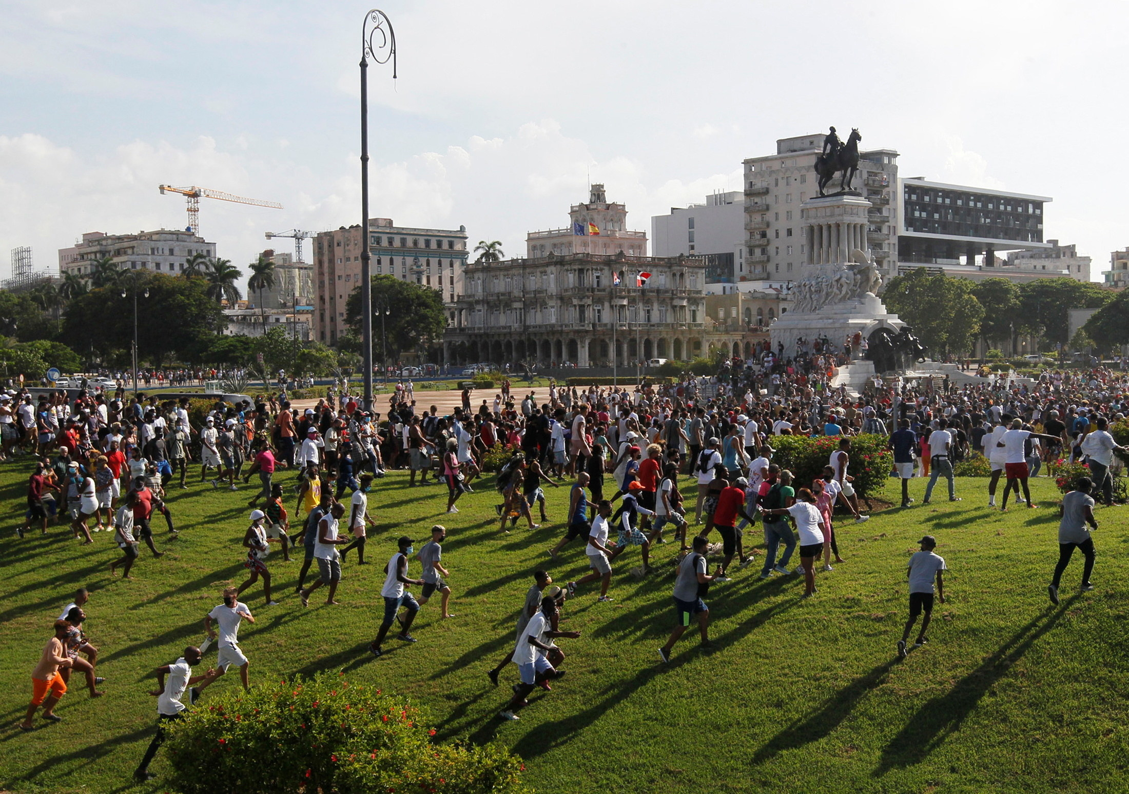 A crowd of people is seen running across the lawn of a government building