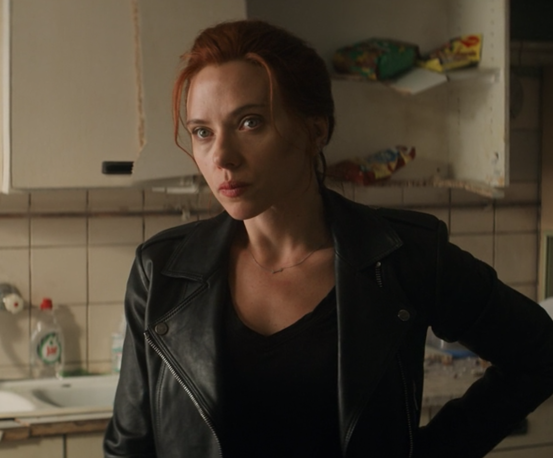 Natasha Romanoff stands with her hand on her hip and her lips pursed