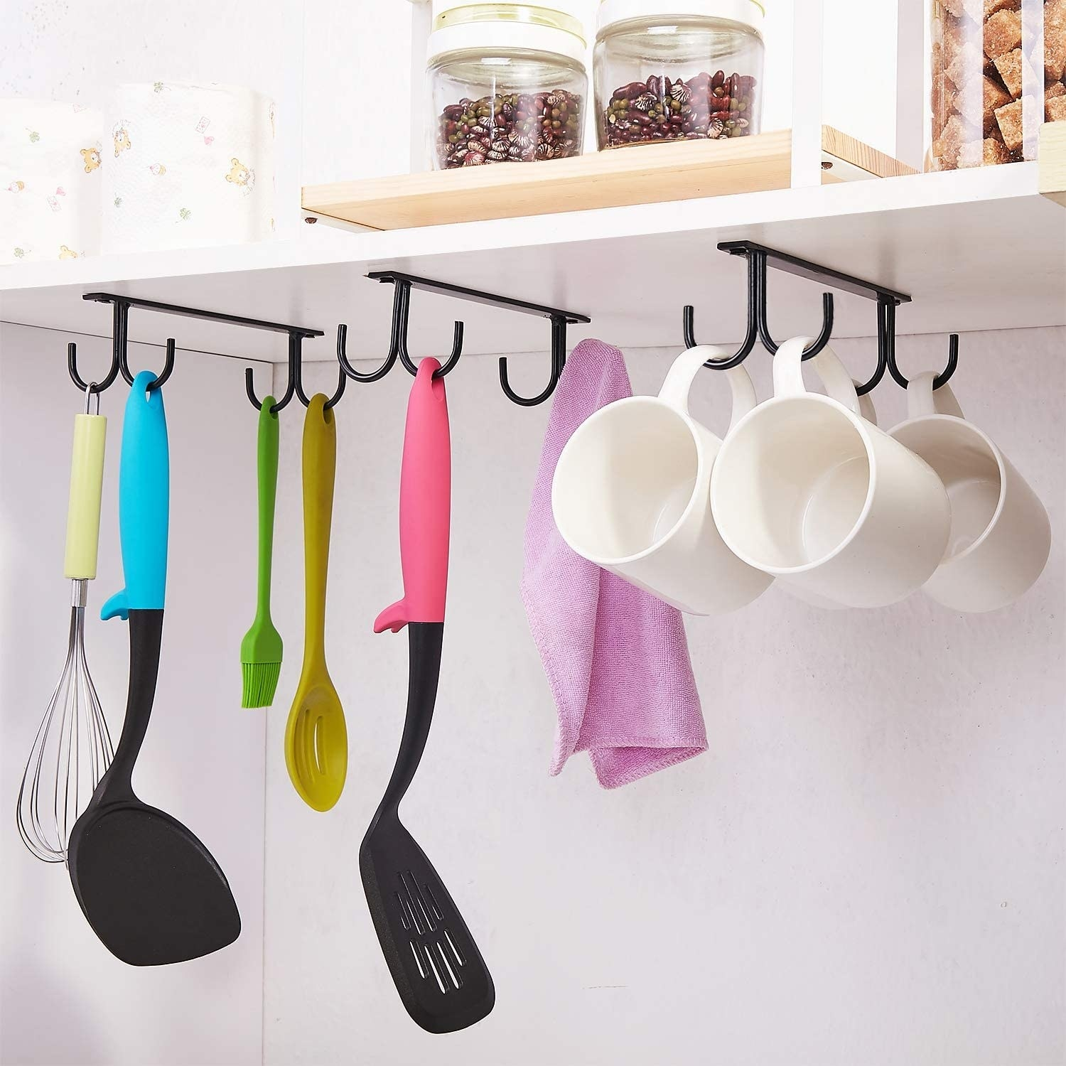 mugs and spatulas hanging off of the mounted hooks