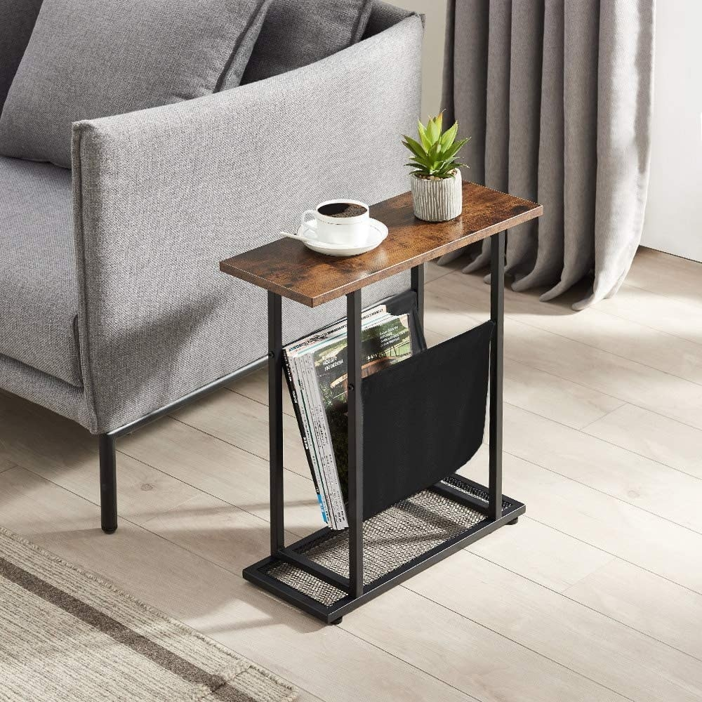 the narrow side table next to a sofa with a plant and a coffee cup on the surface and magazines in the sling