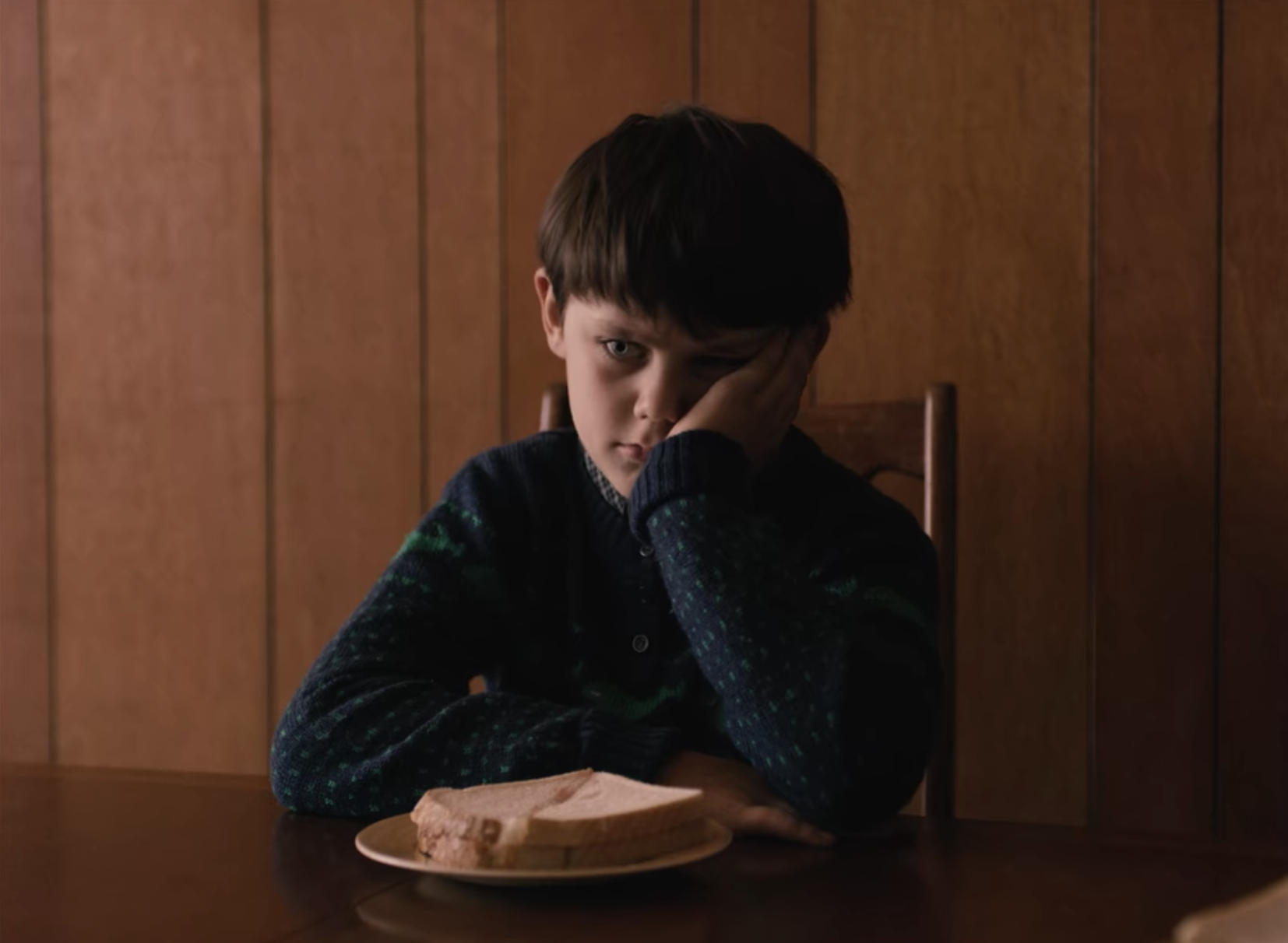 Jack sitting at a table in front of a sandwich with his head in his hand