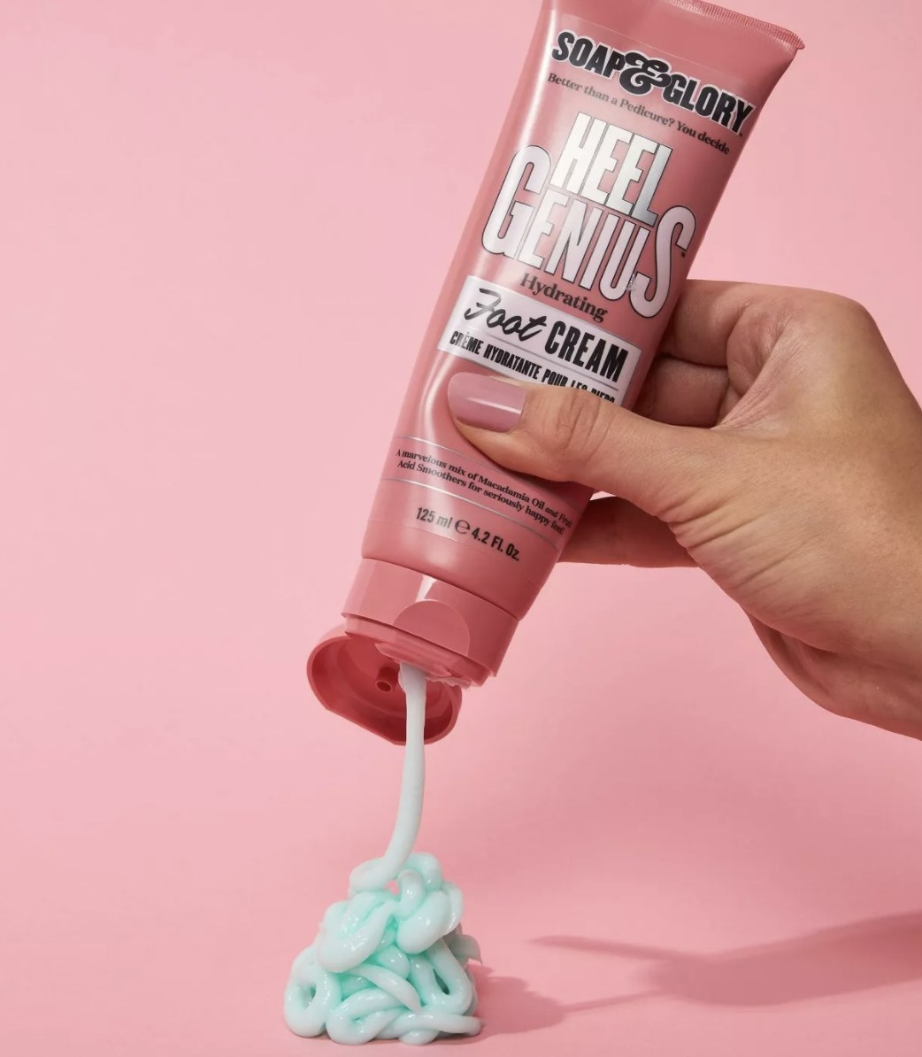 a person squeezing the cream out of its pink tube