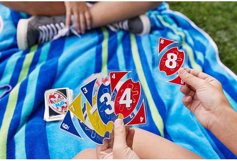 A pack of waterproof cards near a beach towel