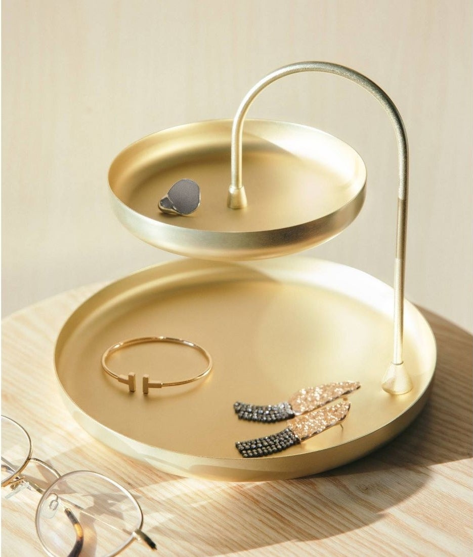 a two-tiered brass jewelry tray