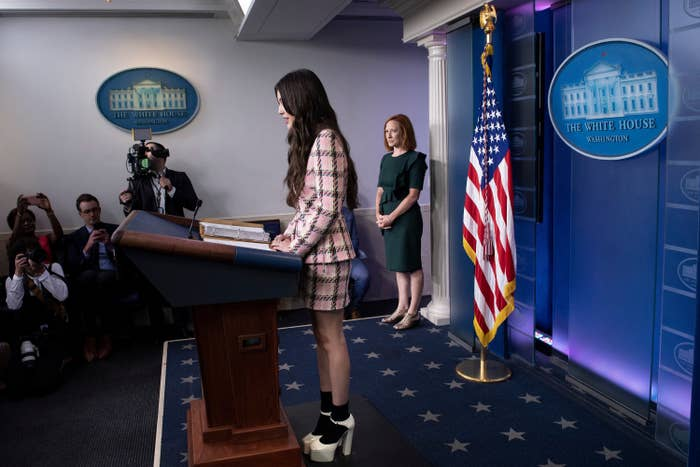 Olivia Rodrigo stands at a lectern in the press briefing room as Jen Psaki looks on